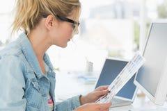 Blonder Herausgeber, der Kontaktblatt auf ihren Schreibtisch betrachtet Lizenzfreies Stockbild