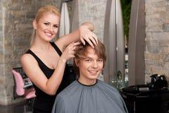 Blonder Herrenfriseur, der Haarkremeisspray anwendet Lizenzfreies Stockfoto
