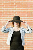 Blonder Hippie, der mit Strohhut gegen orange Ziegelstein backgr aufwirft Lizenzfreies Stockfoto