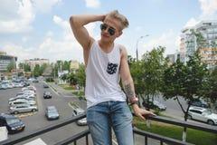 Blonder Hippie-Junge des Porträts mit Tätowierungen und dem stilvollen Haar Stockbilder