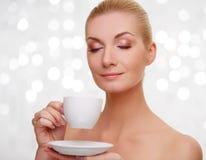Blonder Holding-Tasse Kaffee der jungen Frau Stockfoto