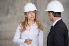 Blonder Ingenieur im Schutzhelm, der Kollegen auf Baustelle betrachtet Stockbild