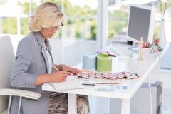 Blonder Innenarchitekt, der an ihrem Schreibtisch arbeitet Stockfotografie