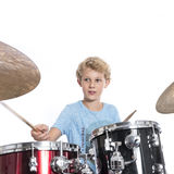 Blonder jugendlich Junge spielt Trommeln am drumkit im Studio gegen weißes Ba Lizenzfreie Stockfotografie