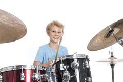 Blonder jugendlich Junge spielt Trommeln am drumkit im Studio gegen weißes Ba Stockfotos