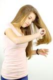 Blonder Jugendlicher, der das lange Haar lokalisiert bürstet Stockfotografie