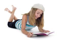 Blonder Jugendlicher, der ein Buch liest Stockbild
