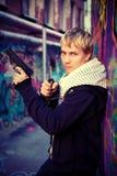 Blonder Jugendlicher, der eine Pistole und ein Messer hält Lizenzfreie Stockbilder