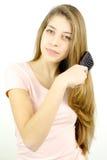 Blonder Jugendlicher mit dem bürstenden Lächeln des sehr langen Haares, Kamera schauend Lizenzfreie Stockfotografie
