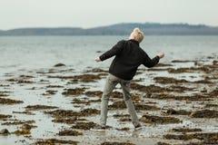 Blonder Junge auf dem Strand, der einen Felsen wirft Stockbild