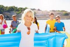 Blonder Junge auf dem Strand mit Freunden Lizenzfreie Stockfotografie