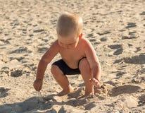 Blonder Junge auf dem Strand spielt mit Sand Stockfotografie