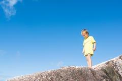 Blonder Junge auf einem Felsen vor blauem Himmel Stockfotografie