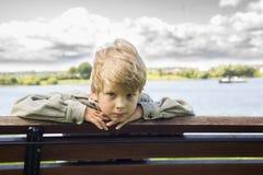 Blonder Junge auf einer Bank im Park auf dem Flusshintergrund Lizenzfreies Stockfoto