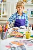 Blonder Junge, der in Art Studio aufwirft Lizenzfreies Stockfoto