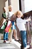 Blonder Junge, der auf Balkon mit Eltern hinten steht Lizenzfreies Stockfoto