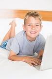 Blonder Junge, der auf Bett unter Verwendung des Laptops lächelt an der Kamera liegt Stockbild