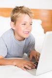 Blonder Junge, der auf Bett unter Verwendung des Laptops liegt Lizenzfreies Stockfoto