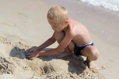 Blonder Junge, der auf dem Strand spielt Stockbild