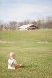 Blonder Junge, der auf einem Feld auf einem Bauernhof sitzt Lizenzfreie Stockfotografie