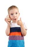 Blonder Junge, der auf Muschel hört Lokalisiert auf Weiß Stockbilder