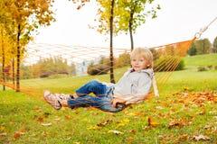 Blonder Junge, der auf Netz der Hängematte im Park legt Lizenzfreie Stockfotografie