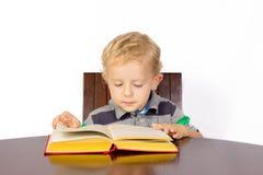 Blonder Junge, der aufmerksam ein Buch liest Lizenzfreie Stockfotos