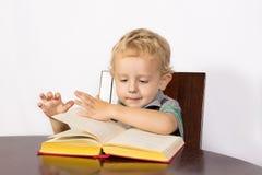 Blonder Junge, der aufmerksam ein Buch liest Lizenzfreies Stockfoto