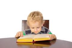 Blonder Junge, der aufmerksam ein Buch liest Stockfotos