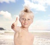 Blonder Junge, der Daumen am Strand aufgibt Stockfoto