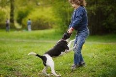 Blonder Junge, der den Spaß spielt mit dem Hund hat Stockbilder