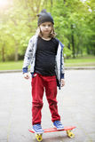 Blonder Junge, der draußen auf Skateboard steht Lizenzfreie Stockbilder