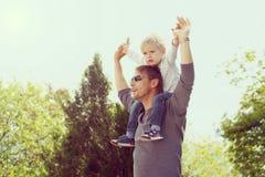 Blonder Junge, der draußen auf Vaterschulter sitzt Stockfoto