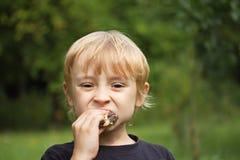 Blonder Junge, der draußen Kuchen isst Stockfoto