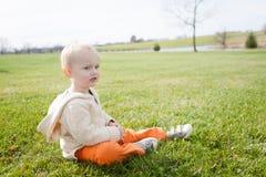 Blonder Junge, der draußen sitzt Stockfotografie