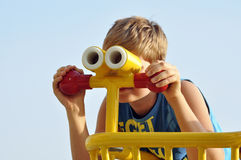 Blonder Junge, der durch das Spielzeug binokular schaut Stockbilder