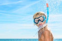 Blonder Junge, der Dusche am Strand nimmt Lizenzfreie Stockfotografie