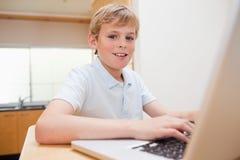 Blonder Junge, der ein Notizbuch verwendet Stockfoto