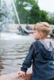 Blonder Junge, der an einem Brunnen steht Lizenzfreie Stockfotos