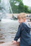 Blonder Junge, der an einem Brunnen steht Stockfotos