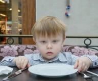 Blonder Junge, der an einem Tisch mit einer leeren Platte sitzt Lizenzfreie Stockfotos