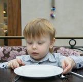 Blonder Junge, der an einem Tisch mit einer leeren Platte sitzt Stockbilder