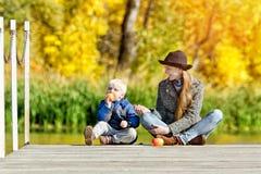 Blonder Junge, der einen Apfel mit ihrer Mutter auf dem Dock isst Sonnig, Herbst Lizenzfreies Stockfoto