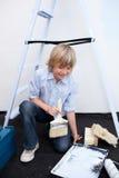 Blonder Junge, der einen Raum mit seinen Muttergesellschaftn malt Stockfotografie
