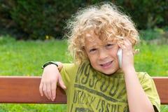 Blonder Junge, der einen Smartphone verwendet Lizenzfreie Stockfotos