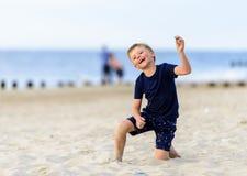 Blonder Junge, der einen Strand genießt Stockfotos