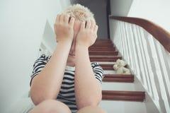 Blonder Junge, der Hände bedrängt, um mit Teddybären gegenüberzustellen Stockfoto