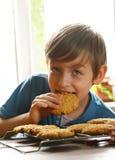 Blonder Junge, der Hafermehlplätzchen isst Stockbilder