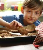 Blonder Junge, der Hafermehlplätzchen isst Stockfotografie