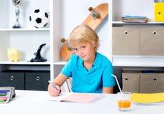 Blonder Junge, der Hausarbeit tut Stockbild